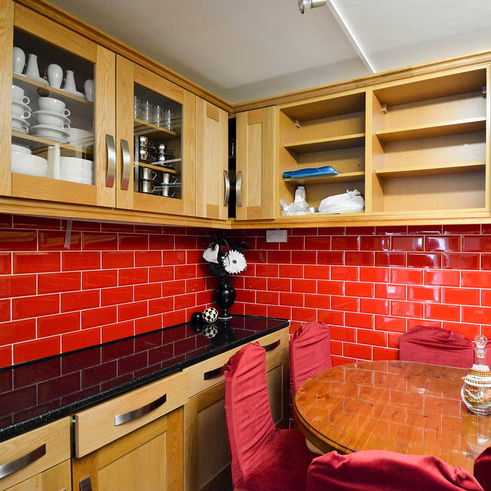 Red tiles inside a kitchen that axis added to a housing property