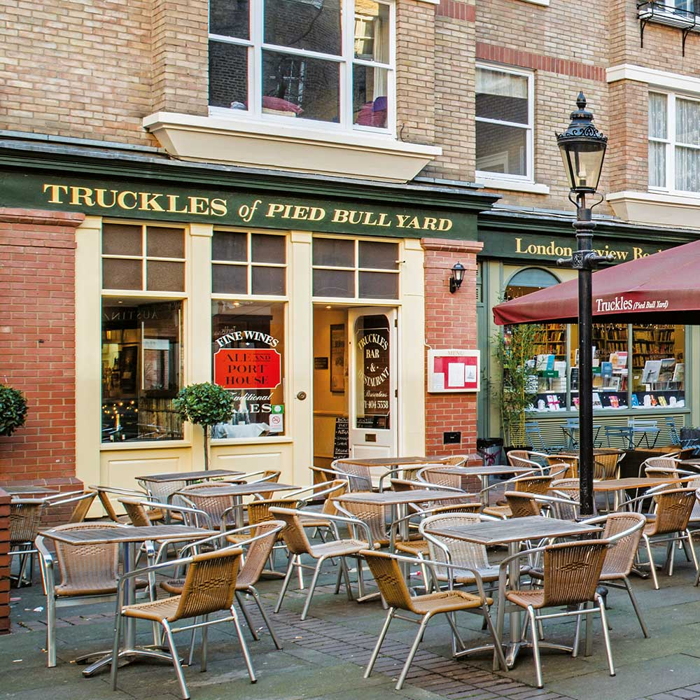 Bar and restaurant with tables and chairs in front of a London heritage space after axis refurbishment