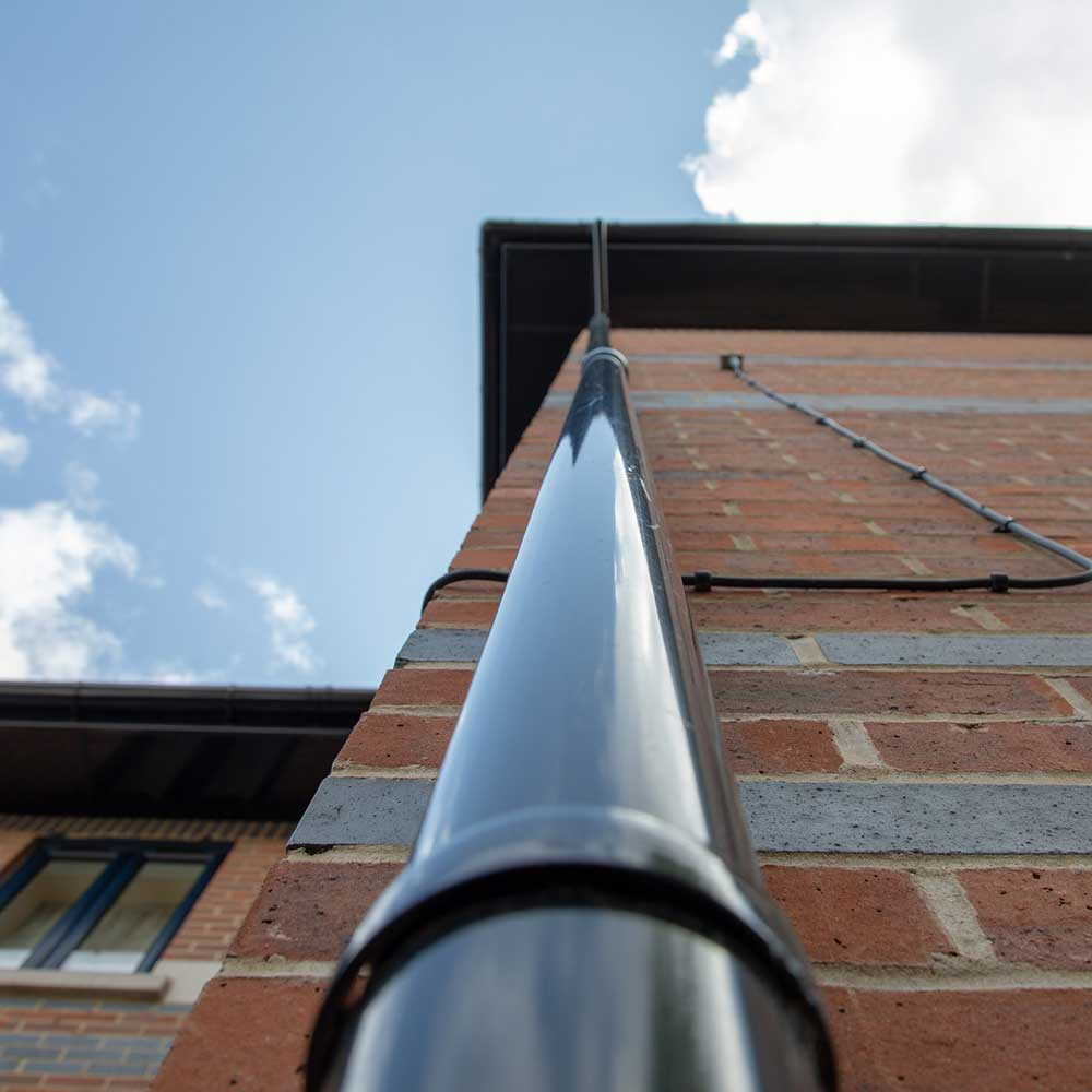 Gutter pipe on the side of a housing block after refurbishment works