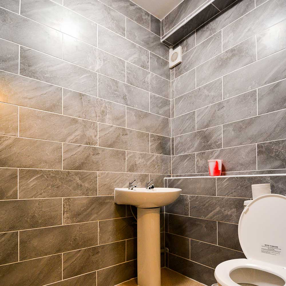 Bathroom with grey tiles inside a housing property after axis added an extension