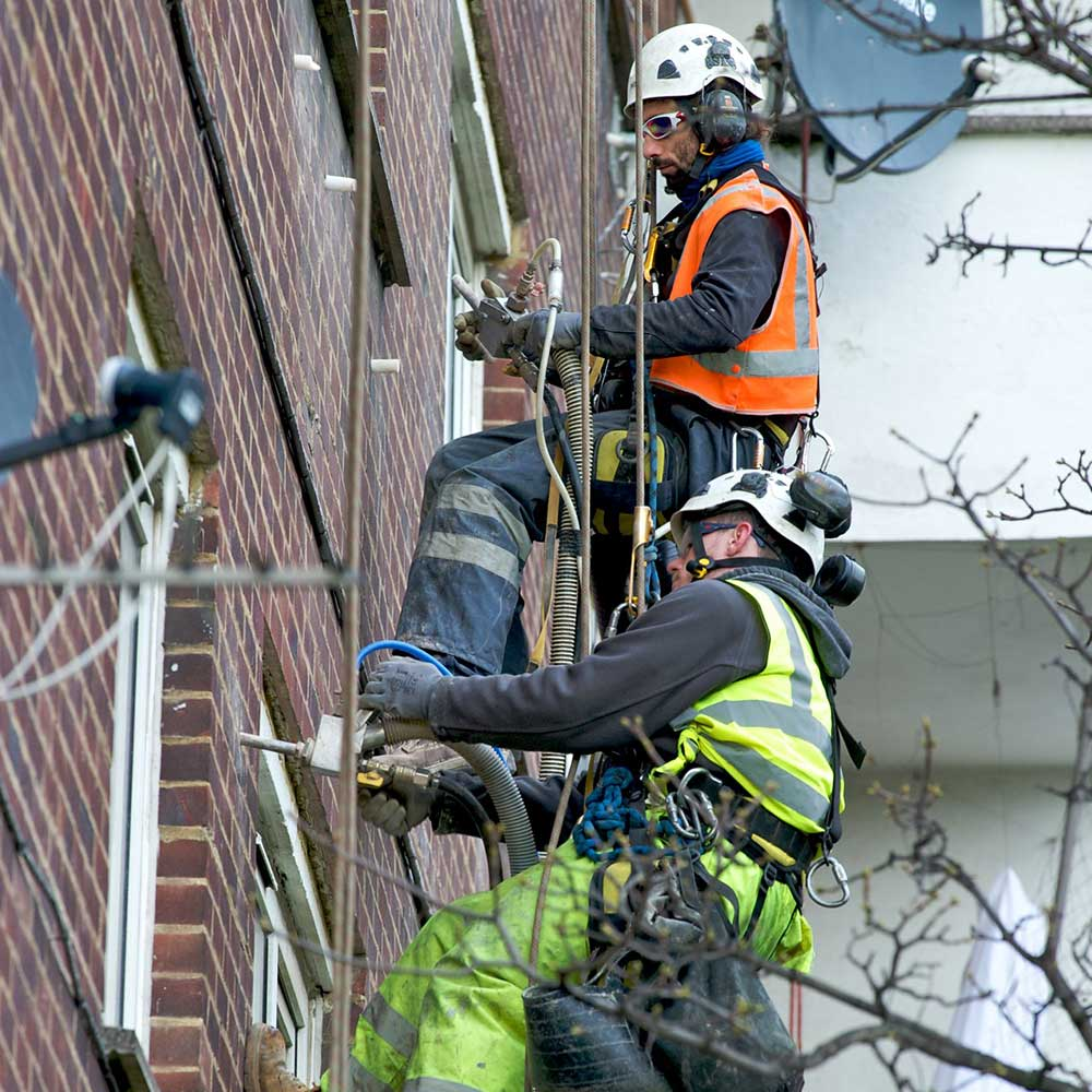 2 axis people work together while abseiling the side of a block of flats