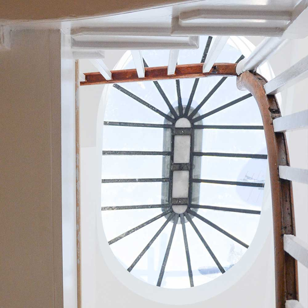 Skylight above a staircase with a wooden bannister inside a new office conversion project