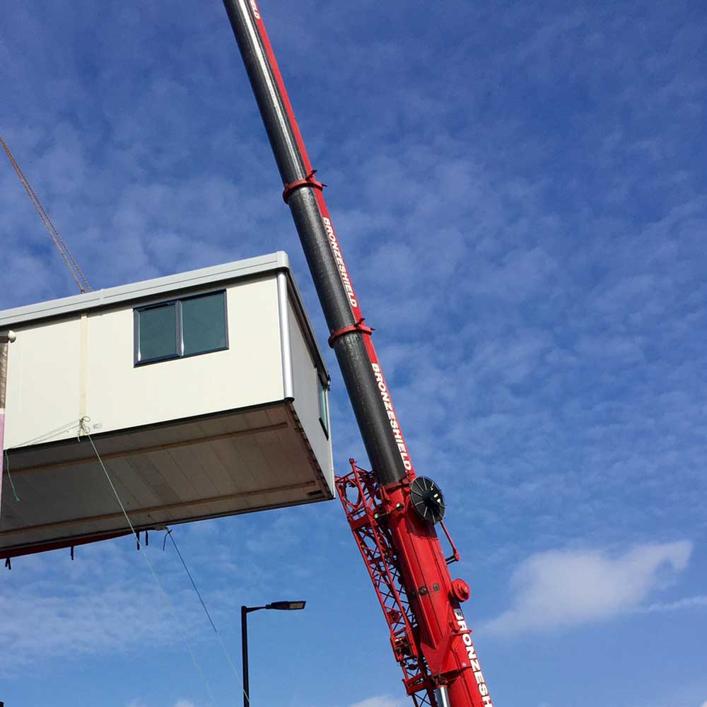 Large crane lifting a modular building in the air