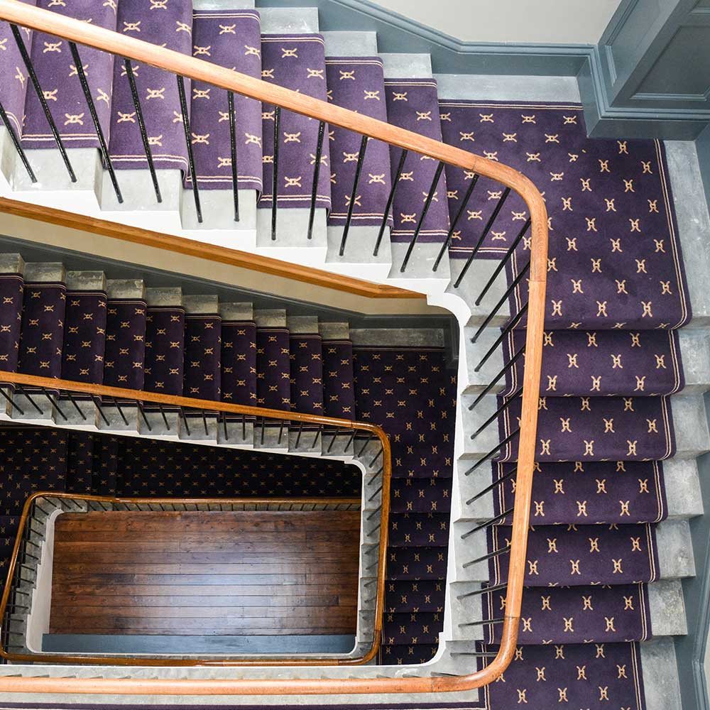 Staircase with purple carpet and wooden banisters inside a listed building after repair works