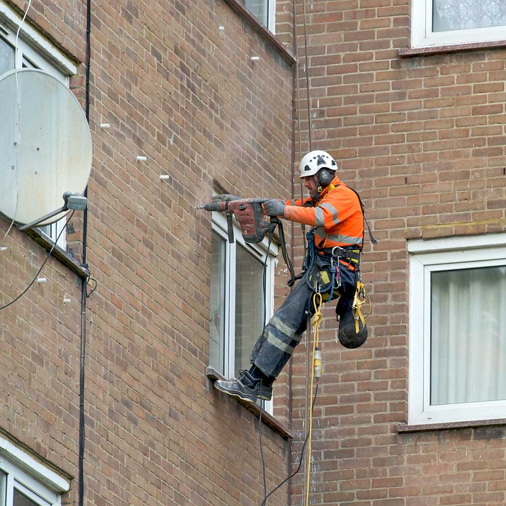 Axis man drills into a wall to repair cavity insulation