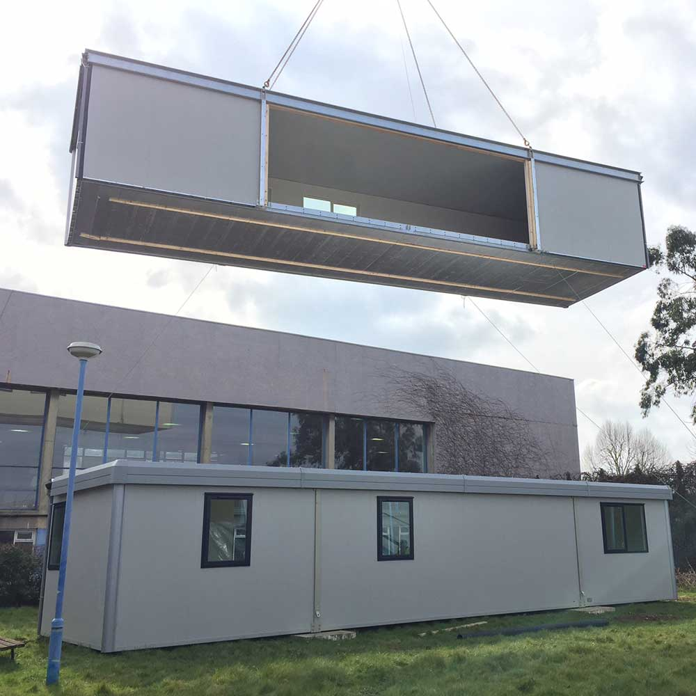 Modular building being lifted into place during installation process