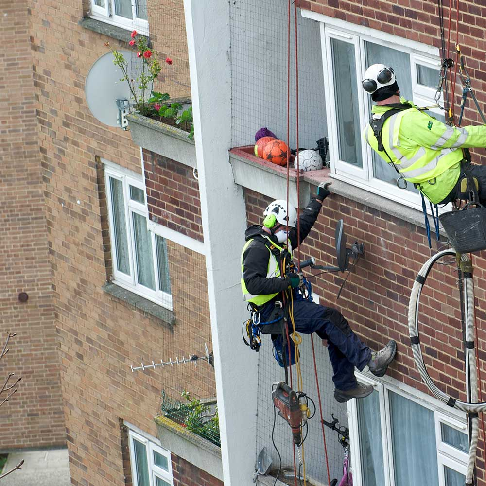 2 axis people repair a cavity wall whilst abseiling