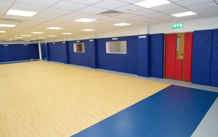 Gymnasium with blue padded walls after a large renovation