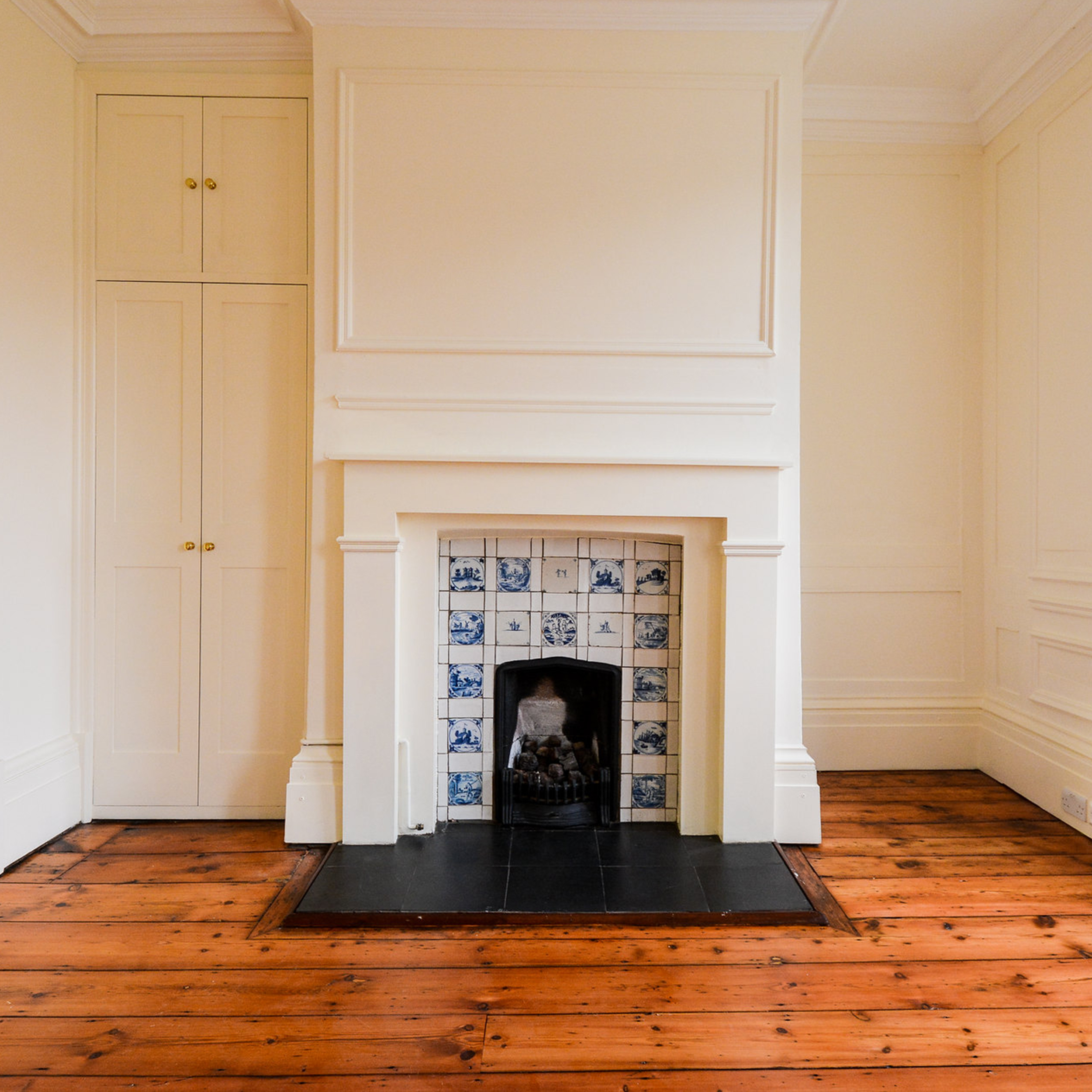 Void property with a large fireplace and wooden floorboards