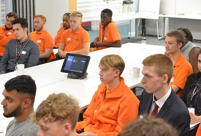 Axis apprentice welcome event shows apprentices sitting