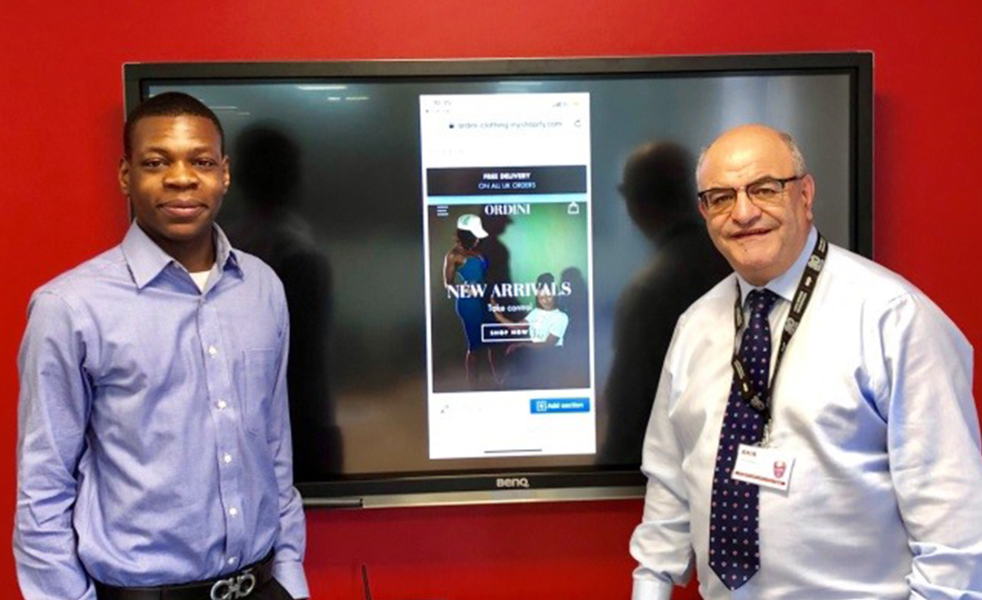 Joe Ibrahim and Chris Ngoma standing Infront of tv promoting online business