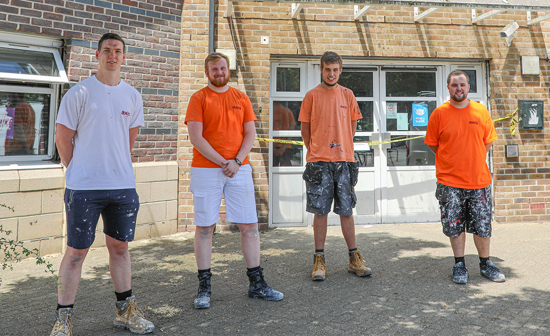 Axis apprentices standing outside a community Action centre