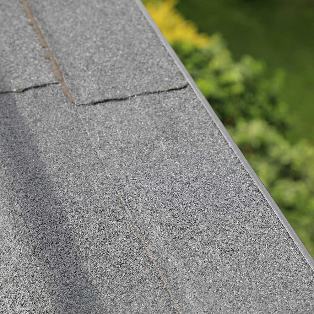 Green grass is seen beside a newly refurbished roof